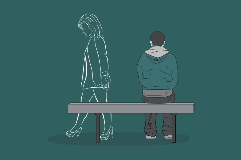A sad man sits alone on a bench as he thinks about his ex-partner.